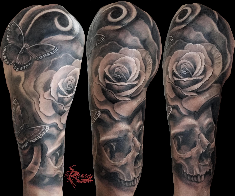 Tatuaggio realistico con teschio, rosa e farfalla