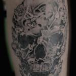 Tattoo teschio creato con elementi floreali e farfalle